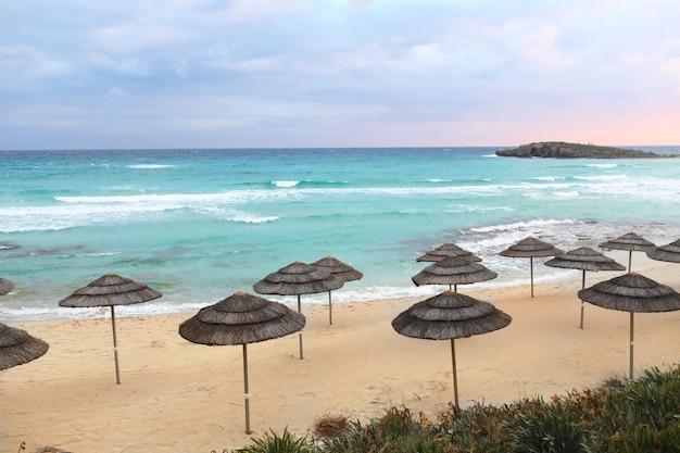 Соломенные зонтики на пляже с морем голубое небо с закатом. никто. чистый горизонт. выборочный фокус. копировать пространство