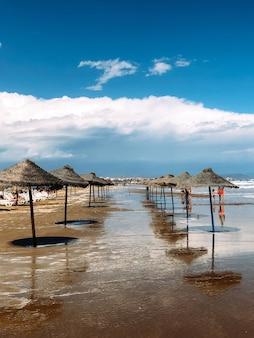 Straw umbrellas on wet beach