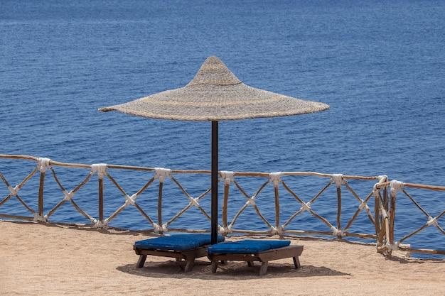 이집트 샤름 엘 셰이크 리조트의 모래 해변에 있는 붉은 바닷물 옆에 나무 일광욕용 라운저가 있는 밀짚 우산