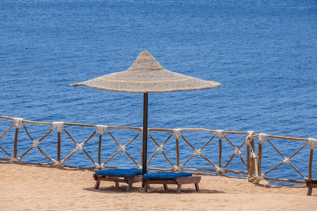 Straw umbrellas with wooden sun loungers next to the sea water on sand beach egypt