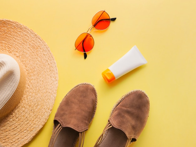 Straw woman's hat with sun glasses, protection cream and sandals top view bright yellow background flat.