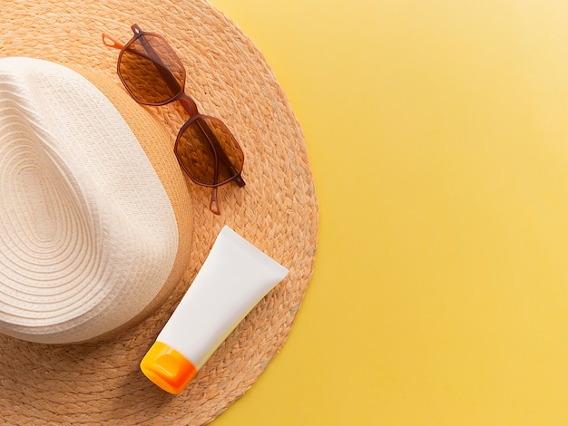 Straw woman's hat with sun glasses and protection cream top view bright yellow background flat.
