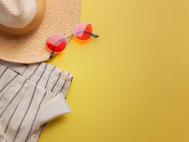 Straw woman's hat with sun glasses and shorts top view bright yellow background flat lay single.