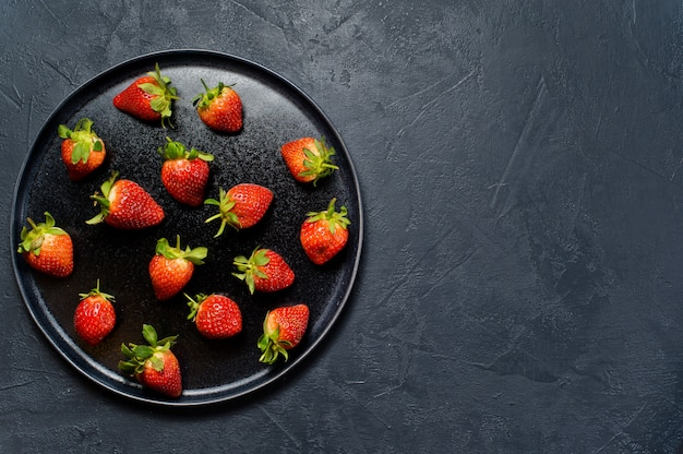 Strawberries on a black plate.