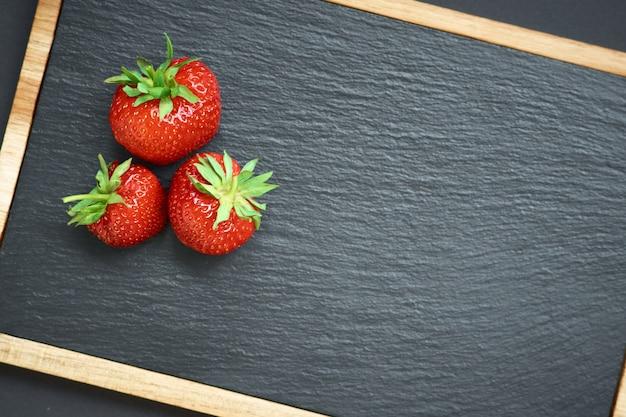 Strawberries on black stone board.