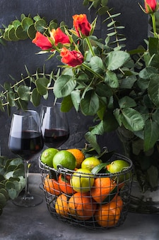 Strawberries and blackberries in a green plate and mandarines  in a basket near a vase with a rose bouquet, on a black background. two glasses of red wine