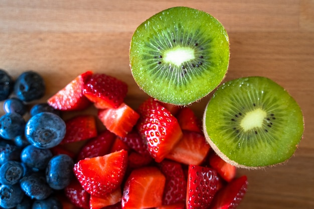 Strawberries, blueberries and kiwis in a wood table