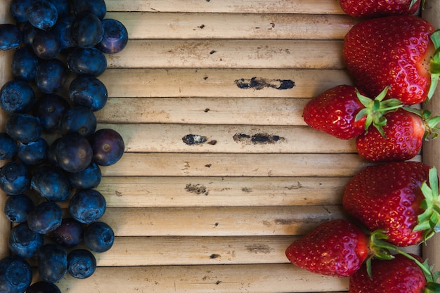 Strawberries and blueberries opposite each other on wooden surface