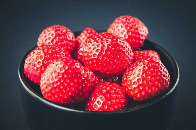 Strawberries in a bowl. black background. studio shooting