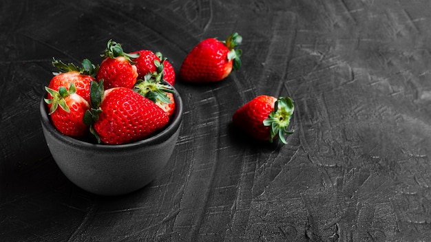 Strawberries in bowl on black table