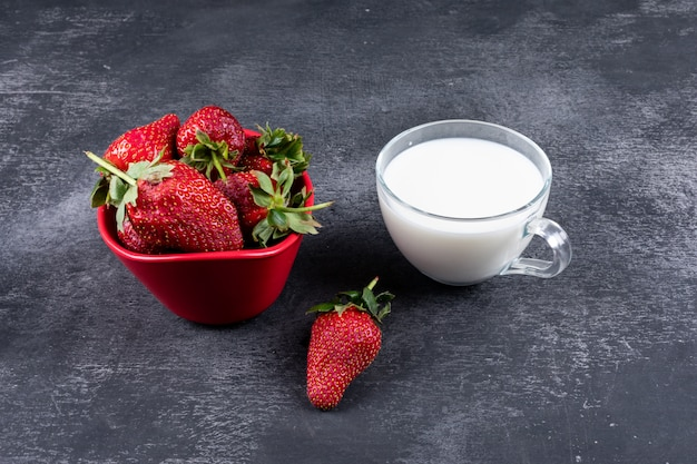 Strawberries in bowl and others around with a cup of milk on dark table