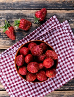 Strawberries in a bowl on a picnic cloth and wooden table. top view.