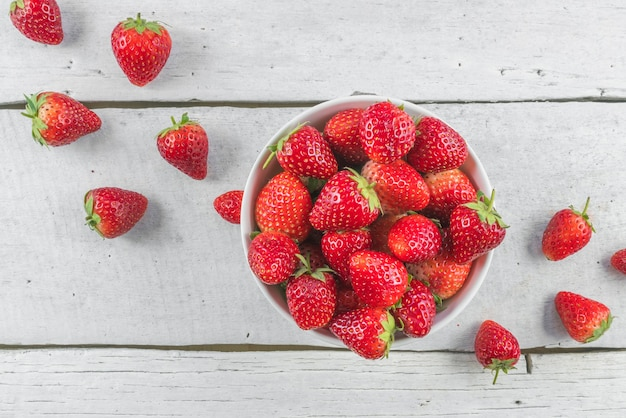 Strawberries in bowl on white table top view.