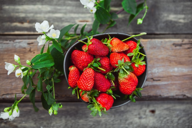 Strawberries in a bowl with flower branch top view on old wooden table