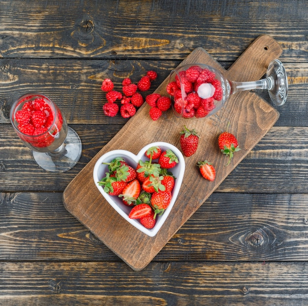 Strawberries in bowl with raspberries in glasses