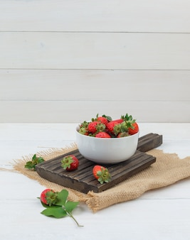 Strawberries in a bowl on wooden board