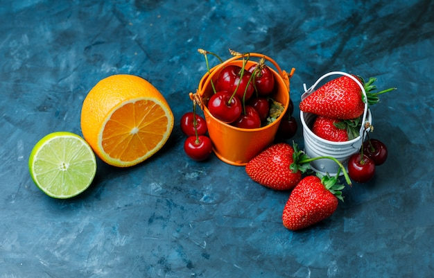 Strawberries and cherries in mini buckets with orange, lime flat lay on a grungy blue background