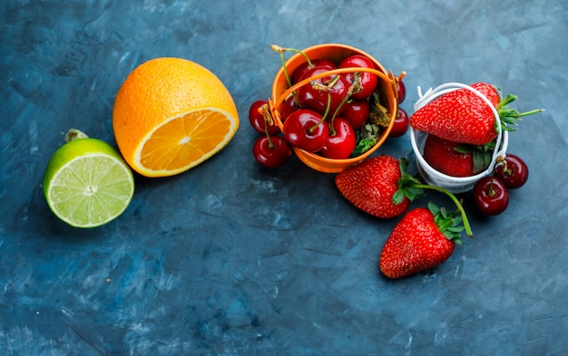 Strawberries and cherries with orange, lime in mini buckets on grungy blue background, flat lay.