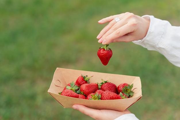 딸기는 일회용 에코 접시에 닫혀 있고 여성의 손은 흐릿한 배경에서 하나를 집어들다
