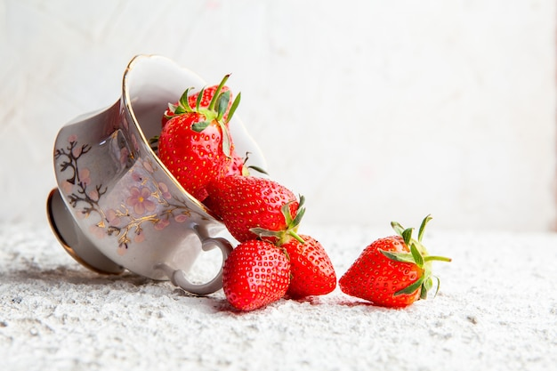 Strawberries in a coffee cup on a white textured background. side view. space for text