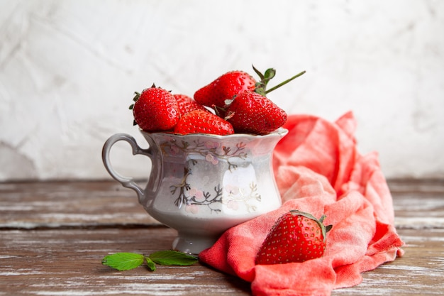 Strawberries in a coffee cup with red cloth side view on a wooden and white background space for text