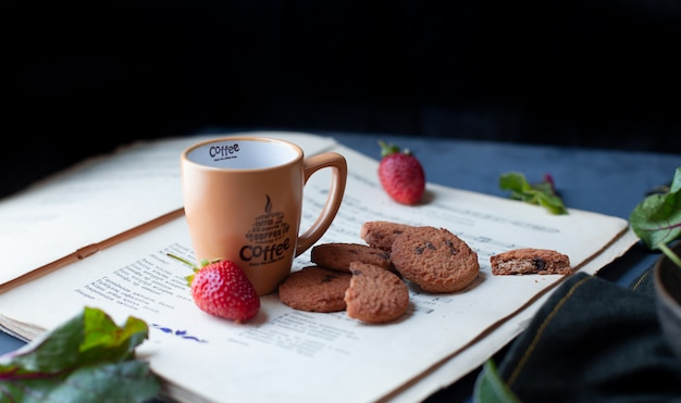 Strawberries, cookies and coffee cup on a book paper.