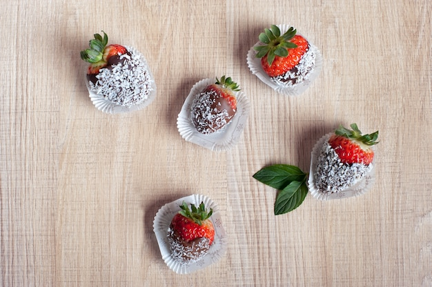 Strawberries covered with chocolate and coconut flakes