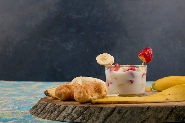 Strawberries in cream served with banana and puff pastries