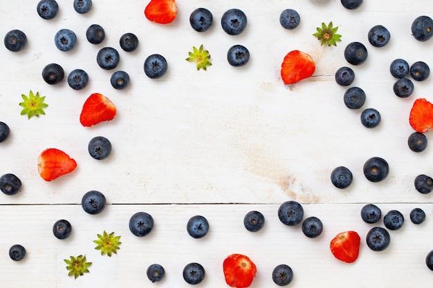 イチゴは半分にカットされ、ブルーベリーはフレームの境界に配置され、白い木製のテーブルの中央にコピースペースがあります。