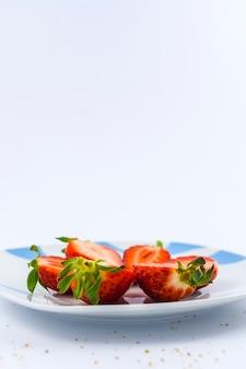 Клубнику нарезать белой тарелкой на белом с коричневым сахаром