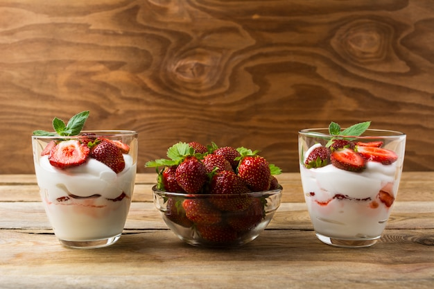 Strawberries dessert with whipped cream on rustic wooden background