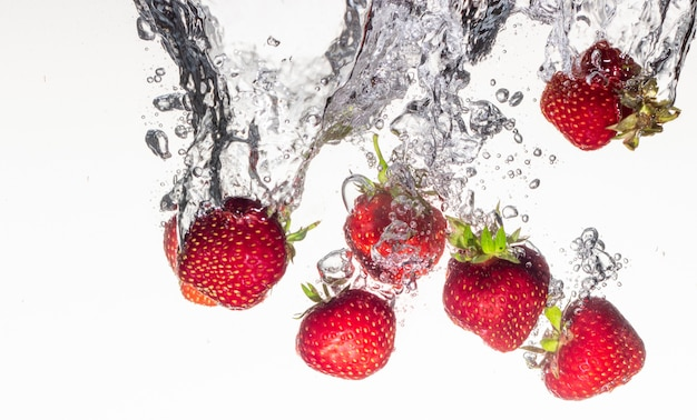 Strawberries falling into the water on a white