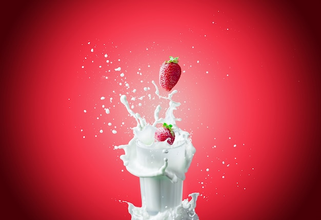 Strawberries falls in milk