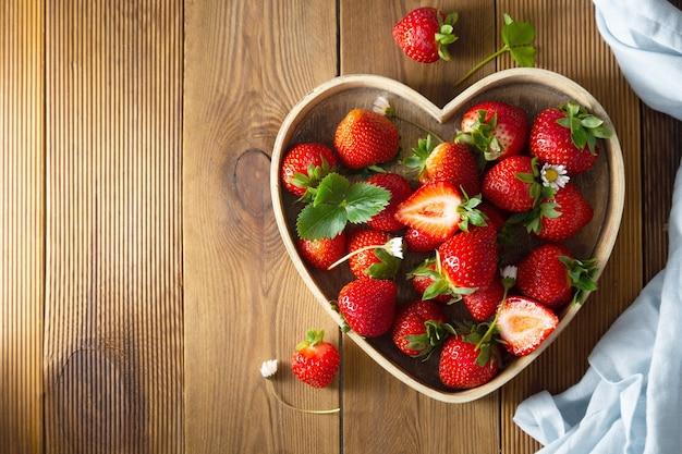 Плоды клубники в деревянной посуде. деревенский летний фруктовый фон.