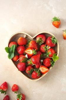 Плоды клубники в деревянном блюде в форме сердца. яркий фон, вид сверху. скопируйте пространство. Premium Фотографии