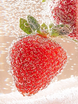 Strawberries in a glass container with bubbles in neon toning with gradient