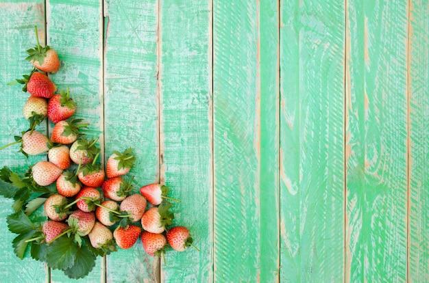 Strawberries on green wooden floor