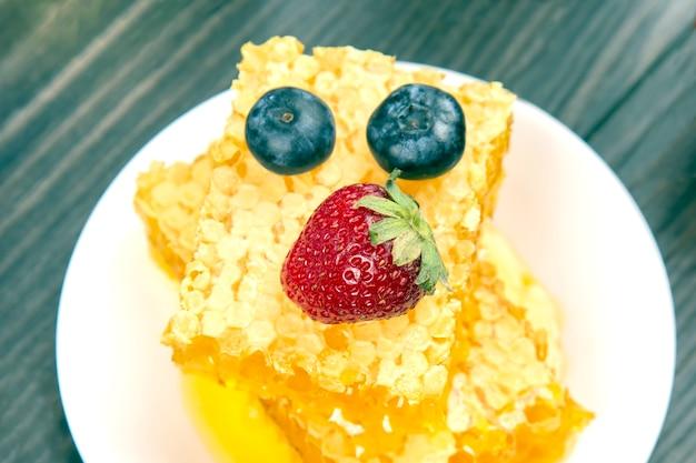 딸기, holubika는 신선한 벌집에 놓여 있습니다. 비타민 유기농 식품