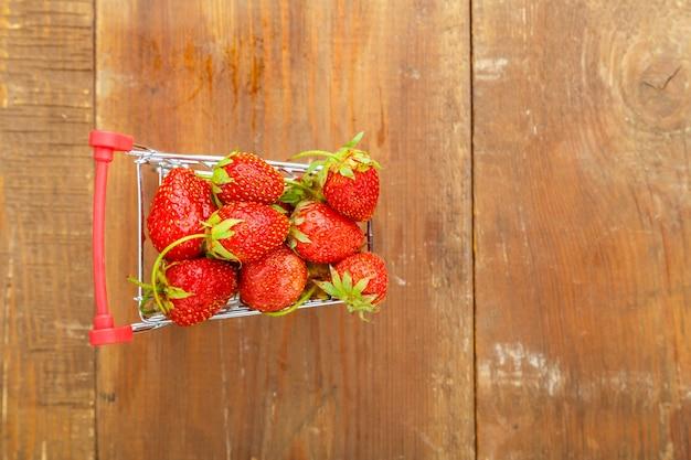 나무 배경에 식료품 카트에 딸기입니다.