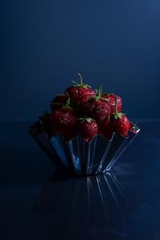 진한 파란색 배경에 금속 접시에 딸기. 미니멀리즘