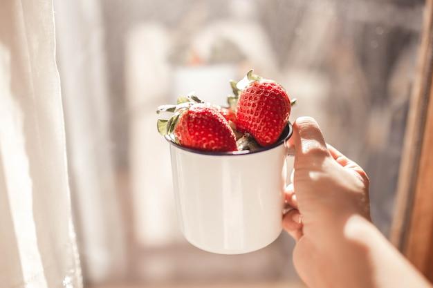 하얀 에나멜 머그잔과 한 딸기