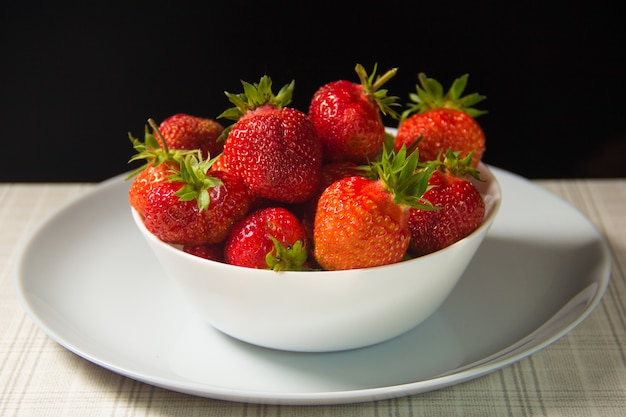 하얀 접시에 딸기입니다. 흰색 배경에 고립 된 딸기의 그룹