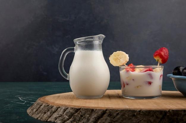 Клубника в сливках, подается с молоком и вишней на черном фоне