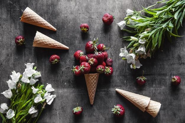 Клубника в чашках на темно-сером фоне с вафлями и белыми цветами. здоровое питание, фрукты