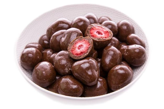 Клубника в темном шоколаде, конфеты в белом блюде крупным планом