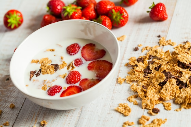木製のミルクのイチゴ。健康的な朝食