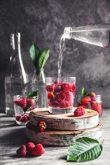 濃い灰色の背景に水中のイチゴ。健康食品、果物。装飾としての花の花束