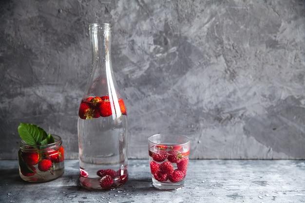暗い灰色の背景の上に水のイチゴ。健康食品、フルーツ。装飾としての花の花束
