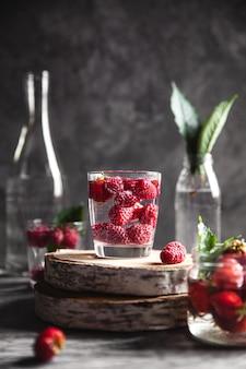 濃い灰色の水中のイチゴ。健康食品、果物。装飾としての花の花束