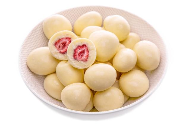 Клубника в белом шоколаде в светлой тарелке на белом фоне изолированные продукты в белом блюде на белом фоне изолированные предметы и продукты